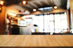 Пустая деревянная таблица с запачканной монтажом предпосылкой кафа кофе стоковые фото