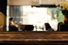 Пустая деревянная таблица с запачканной предпосылкой сделанной с винтажными тонами, предпосылкой нерезкости кофейни с bokeh стоковое фото rf