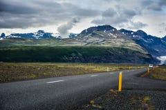 Пустая дорога асфальта в Skeidararsandur с одиночным автомобилем Стоковые Изображения RF