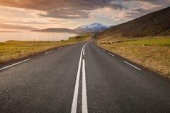 Пустая дорога в северной Исландии на заходе солнца стоковые изображения