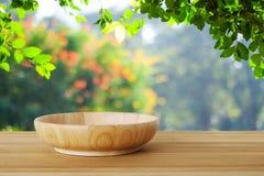 Пустая деревянная плита на таблице над деревьями нерезкости с backgroun bokeh Стоковое Изображение RF