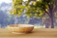 Пустая деревянная плита на таблице над деревьями нерезкости с backgroun bokeh Стоковые Изображения RF