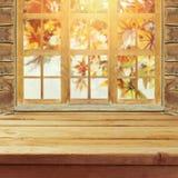 Пустая деревянная таблица палубы над предпосылкой bokeh листьев wndow и осени Стоковое Изображение