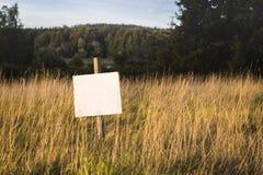 Пустая земля для продажи подписывает внутри идилличный ландшафт стоковое фото
