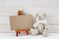 Пустая карточка на миниатюрных мольберте и плюшевом медвежонке Стоковое Фото