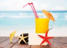 Пустая карточка, стекло оранжевого коктеиля и морские звёзды на море Стоковая Фотография RF