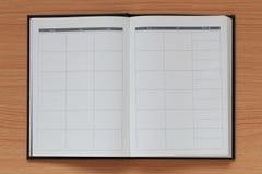 Пустая книга помещена на коричневой деревянной предпосылке Стоковая Фотография