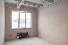Пустая комната с окном и батареей в доме под конструкцией, заштукатуренными стенами, screed на поле, конкретное многоуровневом стоковая фотография rf