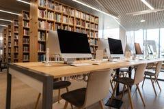 Пустая компьютерная комната в школьной библиотеке Современные компьютеры стоят на деревянном столе стоковые фото