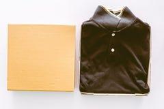 Пустая коробка и черная рубашка на белой предпосылке Стоковые Фото