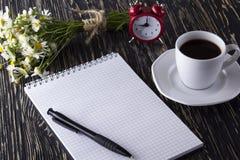 Пустая кофейная чашка тетради, будильника, charmomile и Стоковое Фото