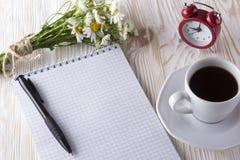 Пустая кофейная чашка тетради, будильника, charmomile и Стоковая Фотография