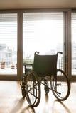 Пустая кресло-коляска в живущей комнате рядом с креслом Стоковое Фото