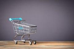 Пустая магазинная тележкаа супермаркета на серой предпосылке с космосом экземпляра стоковое фото
