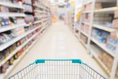 Пустая магазинная тележкаа с абстрактным супермаркетом нерезкости Стоковые Фото