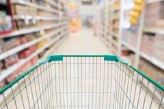 Пустая магазинная тележкаа с абстрактным супермаркетом нерезкости Стоковая Фотография