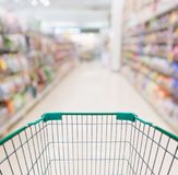 Пустая магазинная тележкаа с абстрактным супермаркетом нерезкости Стоковое фото RF
