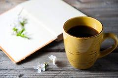 Пустая обложка книги на деревянной предпосылке с цветком весны и накидкой кофе Стоковые Изображения