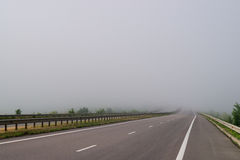 Пустая дорога в тумане Стоковые Фотографии RF