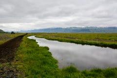 Пустая дорога с взглядом к горе с малым рекой на всем пути стоковая фотография