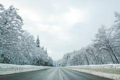 Пустая дорога с высоким уровнем снега покрыла ландшафт в сезоне зимы Стоковые Изображения RF