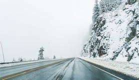 Пустая дорога с снегом покрыла ландшафт в сезоне зимы Стоковые Фото