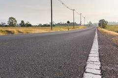Пустая дорога с столбом электричества в пригородном в Таиланде Стоковые Изображения RF