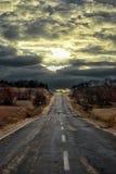 Пустая дорога через заход солнца Стоковое фото RF