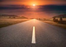 Пустая дорога через пейзаж горы на идилличном заходе солнца стоковая фотография rf