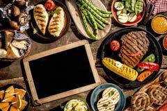 Пустая доска на деревянном столе с зажаренной едой Стоковое фото RF