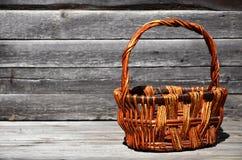 Пустая плетеная корзина деревянных штаног лежит на деревянной поверхности Стоковые Фото