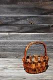 Пустая плетеная корзина деревянных штаног лежит на деревянной поверхности Стоковое Изображение