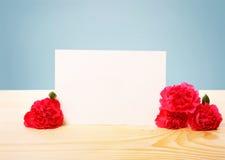 Пустая поздравительная открытка с цветками гвоздики на таблице Стоковые Изображения