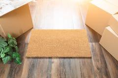 Пустая радушная циновка, Moving коробки и завод на трудных деревянных полах Стоковые Изображения