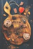 Пустая разделочная доска украшенная с булочками со сливк шоколада, миндалинами и частями шоколада Деревенский тип Булочки сливк стоковое изображение rf