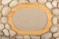 Пустая рамка светлой древесины и белых камней в песке скопируйте космос Стоковое Фото