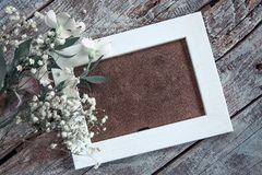 Пустая рамка фото и белые цветки над предпосылкой деревянного стола стоковое фото