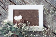 Пустая рамка фото и белые цветки над предпосылкой деревянного стола стоковая фотография rf