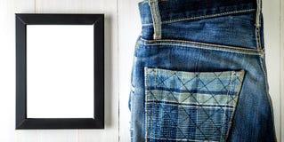 Пустая рамка фото на деревянном столе с джинсами Рамка пробела темы фотографии улицы Стоковая Фотография RF