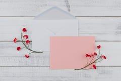 Пустая розовая карточка и белый конверт украшают с красными бумажными цветками Стоковая Фотография