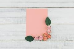 Пустая розовая карточка украшает с цветками розы пинка бумажными и листьями зеленого цвета Стоковая Фотография RF