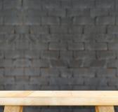 Пустая светлая деревянная таблица и кирпичная стена нерезкости черная в предпосылке, m Стоковые Изображения