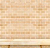 Пустая светлая деревянная таблица и кирпичная стена нерезкости оранжевая в предпосылке, Стоковые Фото