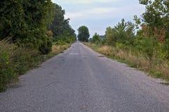 Пустая сельская проселочная дорога асфальта Стоковые Изображения