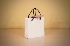 Пустая сумка подарка белой бумаги при насмешка смычка вверх стоя на древесине Стоковая Фотография RF