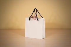 Пустая сумка подарка белой бумаги при насмешка смычка вверх стоя на древесине Стоковые Изображения RF