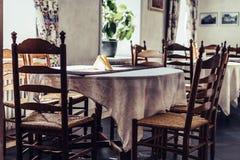 Пустая таблица ресторана в гостинице с желтыми салфетками на ей - сиденье у окна с ярким светом стоковые изображения