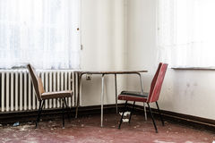 Пустая таблица и 2 стуль в грязной комнате стоковые изображения