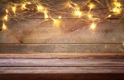 пустая таблица перед гирляндой золота рождества теплой освещает Стоковое Изображение RF