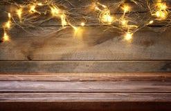 пустая таблица перед гирляндой золота рождества теплой освещает Стоковая Фотография